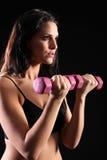 El bicep apto de la mujer joven se encrespa con los pesos del ejercicio Imágenes de archivo libres de regalías