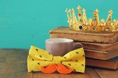 el bigote divertido, la taza de café, el arco y el rey coronan Father& x27; día de s Imágenes de archivo libres de regalías