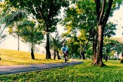 El Biking por la mañana en el carril de la bici del parque público imagenes de archivo