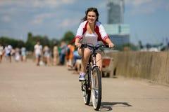 El biking urbano - bici del montar a caballo de la mujer joven Fotografía de archivo