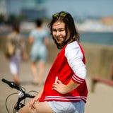 El biking urbano - bici del montar a caballo de la mujer joven Imagenes de archivo
