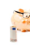 El billete de banco del euro cincuenta delante de la hucha unfocused con los vidrios, concepto para el negocio y ahorra el dinero Imágenes de archivo libres de regalías