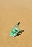 el billete de banco del euro 100 en una botella encontró en la orilla de la playa Imagenes de archivo
