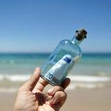 el billete de banco del euro 20 en una botella encontró en la playa Imágenes de archivo libres de regalías
