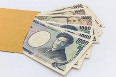 El billete de banco japonés 1.000 y 10.000 yenes en el sobre marrón para da y éxito empresarial y las compras Imágenes de archivo libres de regalías