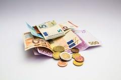 El billete de banco y las monedas euro del dinero aislaron el fondo blanco Foto de archivo