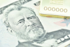 El billete de dólar de Estados Unidos cincuenta, un primer macro con el lingote de oro Fotografía de archivo
