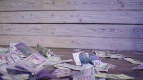 El billete de dólar observa caer a través del aire en un piso de madera y una pared un fondo ibdoor almacen de video