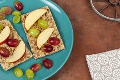 El biscote curruscante plateado remató con las rebanadas de manzana y de uva Fotos de archivo libres de regalías