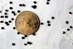 El bitcoin de oro con las joyas negras en el blanco texturizó el fondo fotos de archivo