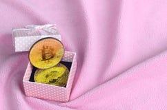 El bitcoin de oro miente en una pequeña caja de regalo rosada con un pequeño arco en una manta hecha de los wi rosas claros suave foto de archivo