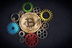 El bitcoin de oro que brilla intensamente entre el diente colorido rueda en fondo negro con el espacio de la copia Cryptocurrency Fotografía de archivo