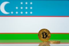 El bitcoin de oro se coloca en un fondo de la bandera del estado de Uzbekistán imagen de archivo libre de regalías