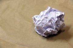 El blanco arrugó la bola de papel en el piso del papel marrón imagenes de archivo