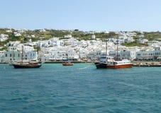 El blanco coloreó la arquitectura griega de las islas en la ladera con los barcos vivos del color en el puerto viejo de Mykonos,  Foto de archivo libre de regalías