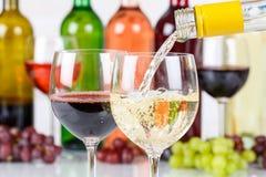 El blanco de colada de la botella de cristal del vino vierte fotografía de archivo libre de regalías