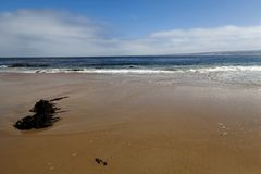 El blanco de las olas oceánicas de la playa de la arena se nubla el cielo azul Foto de archivo libre de regalías