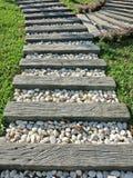 El blanco de madera y pequeño oscila camino en hierba en el jardín Foto de archivo