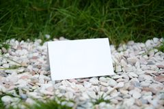 El blanco en blanco dobló el documento sobre las gravas y las hierbas imagen de archivo libre de regalías