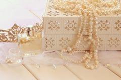 El blanco gotea el collar, la tiara del diamante y la botella de perfume Fotos de archivo libres de regalías