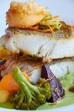 El blanco guisó pescados del pikeperch en salsa verde del pesto con las verduras para cocer el bróculi al vapor, zanahorias, remo foto de archivo