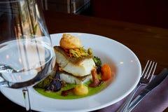 El blanco guisó pescados del pikeperch en salsa verde del pesto con las verduras para cocer el bróculi al vapor, zanahorias, remo fotos de archivo libres de regalías