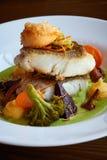 El blanco guisó pescados del pikeperch en salsa verde del pesto con las verduras para cocer el bróculi al vapor, zanahorias, remo fotos de archivo