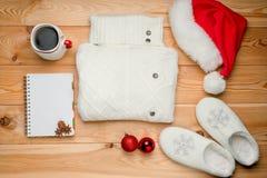 El blanco hizo punto el casquillo del suéter, del ` s de Papá Noel y la taza de café caliente Imagenes de archivo
