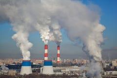 El blanco masivo fuma saliendo de muchas chimeneas de la fábrica foto de archivo libre de regalías