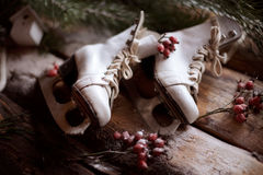 El blanco ol-formó patines en tablones de madera con las ramas spruce y las bayas rojas todo alrededor Imagen de archivo libre de regalías