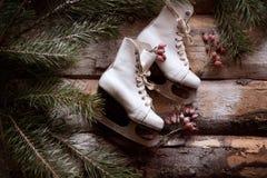 El blanco ol-formó patines en tablones de madera con las ramas spruce y las bayas rojas todo alrededor Fotografía de archivo