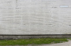 El blanco pintó la pared de madera con la hierba verde como fondo Fotos de archivo