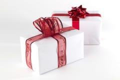 El blanco presenta con las cintas rojas y los arcos, aislados Foto de archivo libre de regalías