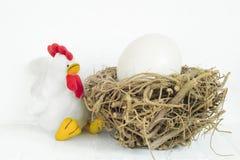 El blanco rellenó el pollo y la jerarquía de madera con dentro grande, enorme el huevo Fotografía de archivo libre de regalías