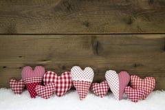 El blanco rojo hecho a mano comprobó corazones en un backgrou de madera de la Navidad Imagenes de archivo
