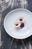 El blanco y la pasta de azúcar de Borgoña florece en la placa blanca Fotografía de archivo