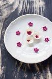 El blanco y la pasta de azúcar de Borgoña florece en la placa blanca Imagenes de archivo