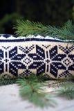 El blanco y el negro hicieron punto el suéter en modelo de la Navidad del invierno en fondo de madera con las ramas del árbol de  imagenes de archivo