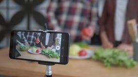 El blog culinario, teléfono móvil hace la grabación de vídeo que es la comida sana viva se preparó de verduras frescas metrajes
