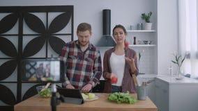El blog video culinario, gente de los bloggers prepara la comida sana con las verduras y verdes en cocina mientras que móvil de l metrajes