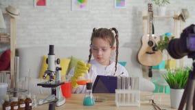El blogger adolescente en una capa blanca y gafas en el laboratorio escribe los resultados del experimento, proyecto de la escuel metrajes