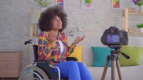 El blogger africano de la mujer inhabilitó en una silla de ruedas con un peinado afro antes del cierre de la cámara para arriba metrajes