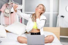 El blogger bonito joven de la muchacha vestido en ropa de moda toma un selfie en su smartphone para su blog que se sienta en fotos de archivo libres de regalías