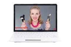 El blogger de la belleza que habla compone cepillos en la pantalla del ordenador portátil es Imagenes de archivo