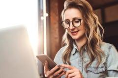 El blogger de la muchacha en vidrios de moda se sienta en café y utiliza smartphone, comprueba el email, comunica con los seguido fotografía de archivo