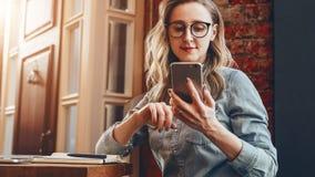 El blogger de la muchacha en vidrios de moda se sienta en café y utiliza smartphone, comprueba el email, comunica con los seguido fotografía de archivo libre de regalías