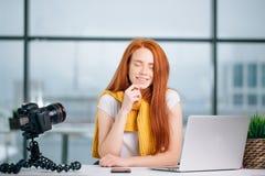 El blogger femenino del pelirrojo feliz con el ordenador portátil piensa en el nuevo tema para el vlog Imagen de archivo libre de regalías
