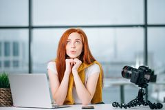 El blogger femenino del pelirrojo feliz con el ordenador portátil piensa en el nuevo tema para el vlog Foto de archivo