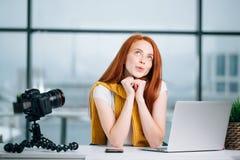 El blogger femenino del pelirrojo feliz con el ordenador portátil piensa en el nuevo tema para el vlog Fotos de archivo libres de regalías