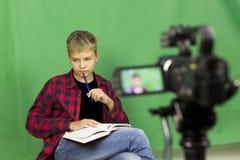 El blogger joven del muchacho registra el vídeo en un fondo verde imagen de archivo